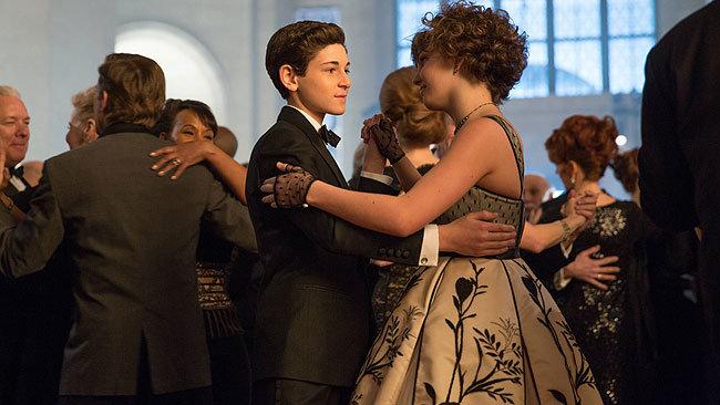 Bruce Wayne y Selina Kyle bailando en la fiesta de caridad.